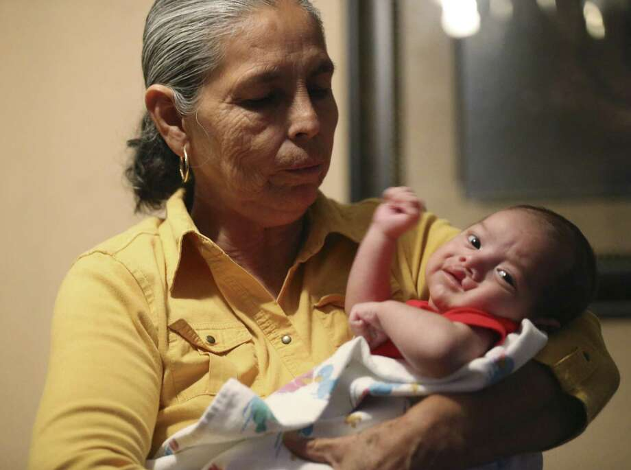 Josefina Peña, 60, carries her seven-week-old grandson, Issac Torres, at her daughter's house in Laredo on Nov. 1, 2017. In April, Peña was transported by ambulance to a San Antonio hospital after complications from heart surgery. At the Laredo checkpoint, she was followed by U.S Border Patrol agents and detained after she was released by the San Antonio hospital. Peña's mother was born in Harlingen but was brought up in Mexico. Peña was born in Mexico and has lived in Laredo for the past five years. Photo: Jerry Lara /San Antonio Express-News / San Antonio Express-News