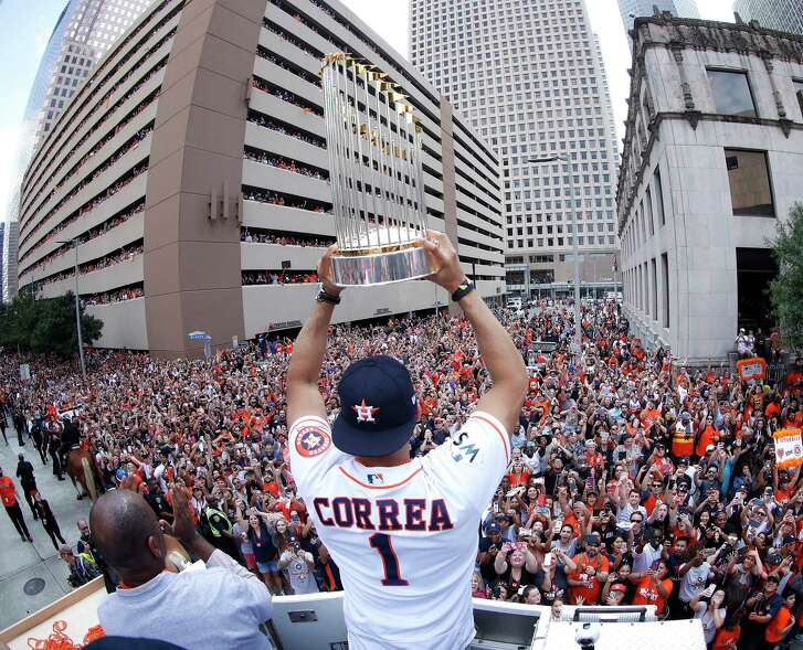 Houston Astros World Series Carlos Correa holds the trophy as he and George Springer joined Mayor Sylvester Turner and Astros owner Jim Crane in the bucket truck of HPD Tower truck 69 during the Houston Astros World Series victory parade downtown on Friday, Nov. 3, 2017, in Houston. ( Karen Warren  / Houston Chronicle )