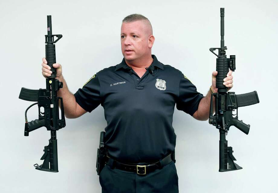 New Haven Police public information Officer David Hartman holds a paintball rife (left) and Colt AR rifle (right) during a press conference at the New Haven Police Department on 9/30/2016. Photo: Arnold Gold / Hearst Connecticut Media