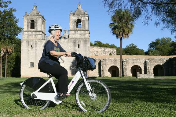 Sister Martha Ann Kirk rides a B-Cycle in front of Mission Concepcion on Oct. 16. Sister Kirk teaches religious studies and is a member of the convent at UIW. She rides a bike along the river on the Mission Reach Hike and Bike Trail nearly every day.