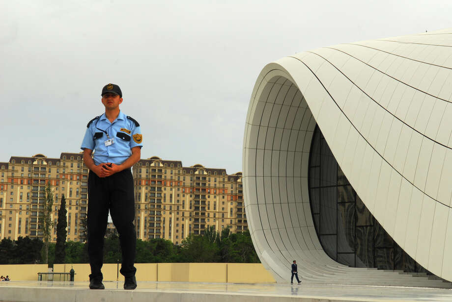 """A security guard stands outside the Heydar Aliyev Center in Baku, Azerbaijan, the site of the 2013  """"US-Azerbaijan Vision for the Future"""" convention organized by Houston businessman Kemal Oksuz. (The Washington Diplomat) Photo: Larry Luxner / The Washington Diplomat"""