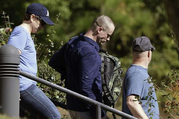 Bowe Bergdahl, center, leaves the Fort Bragg courtroom facility following sentencing at Fort Bragg, N.C., Friday, Nov. 3, 2017. The former Sergeant was spared any prison time and received a dishonorable discharge from the Army. Bergdahl, who walked off his base in Afghanistan in 2009 and was held by the Taliban for five years, pleaded guilty to desertion and misbehavior before the enemy. (AP Photo/Gerry Broome)