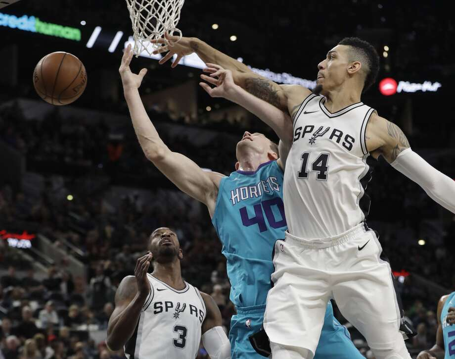 Charlotte Hornets center Cody Zeller (40) has his shot blocked by San Antonio Spurs guard Danny Green (14) as he drives to the basket during the first half of an NBA basketball game, Friday, Nov. 3, 2017, in San Antonio. (AP Photo/Eric Gay)