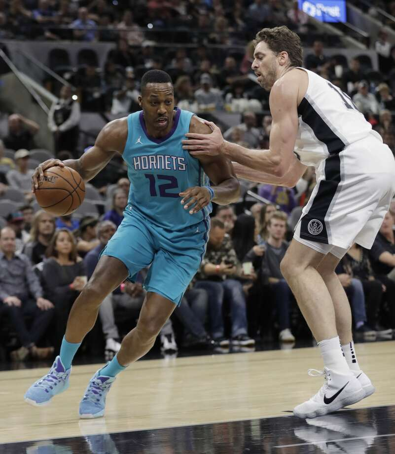 Charlotte Hornets center Dwight Howard (12) drives around San Antonio Spurs center Pau Gasol during the first half of an NBA basketball game, Friday, Nov. 3, 2017, in San Antonio. (AP Photo/Eric Gay)