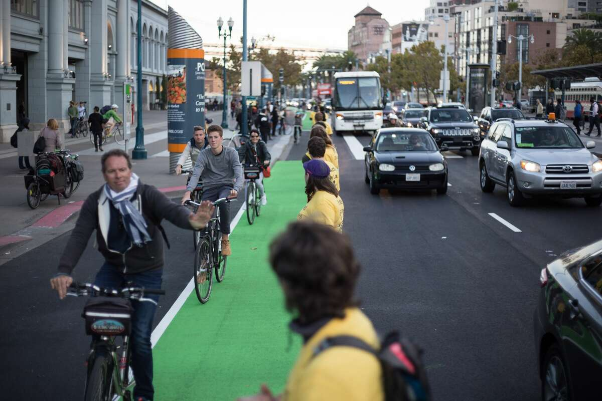Protected bike lane advocates high-fived passing cyclists while forming a barrier between vehicle traffic and the bike lane along the Embarcadero Wednesday night.