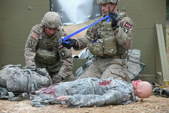 After hacking their way through a sheet metal barrier, Sgt. Joseph Batres, left, and Capt. Chase Morris, work on a dummy during the Army Best Medic Competition at Camp Bullis in San Antonio.
