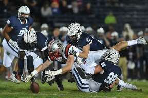 Brown tight end Anton Casey regains a fumble against Yale defensive end Kyle Mullen (98), John Dean (43) and Foyesade Oluokun (23), Friday, Nov. 3, 2017, under the lights at the Yale Bowl in New Haven.
