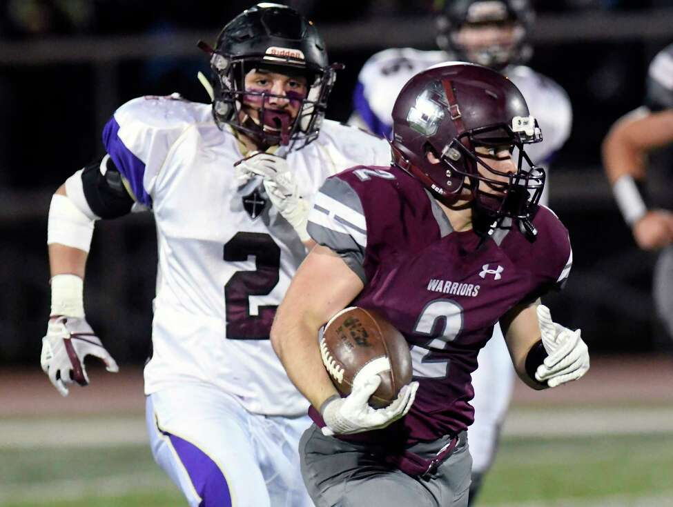 Stillwater's Mason Seymour ,right, runs the ball in front of Holy Trinity Pride's Cameron Kiser during the Section II Class C high school Superbowl football game in Troy, N.Y., Friday, Nov. 3, 2017. Holy Trinity Pride won the game 34-12. (Hans Pennink / Special to the Times Union) ORG XMIT: HP103