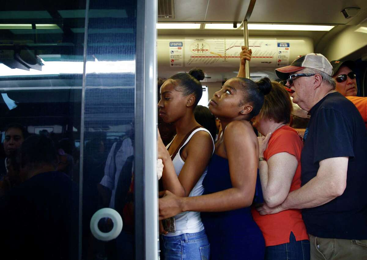 Metro trains already packed with riders leave no room Friday for the hundreds of people waiting in line at the Fannin South Transit Center hoping to catch a free ride downtown for the Astros' championship parade.