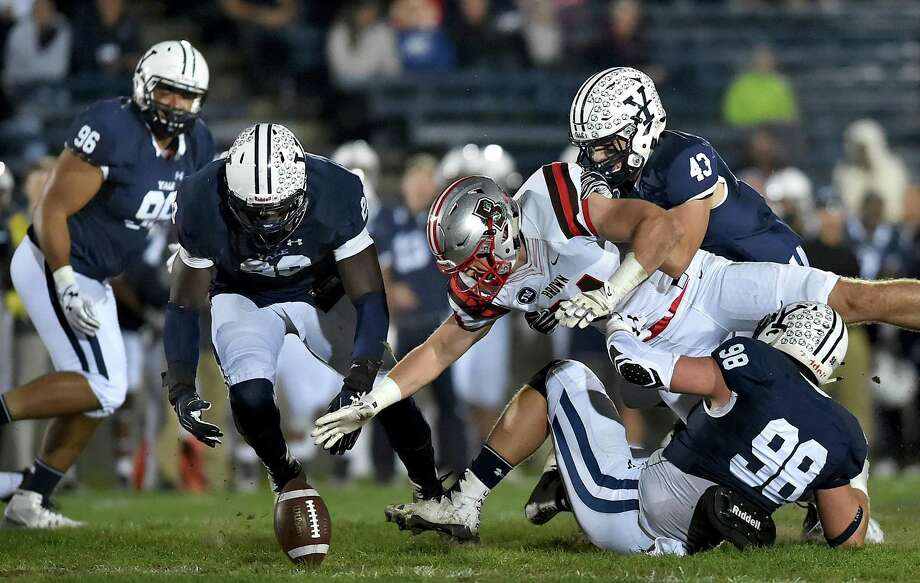 Brown tight end Anton Casey is able to recover a fumble against Yale defensive end Kyle Mullen (98), John Dean (43) and Foyesade Oluokun (23) on Friday under the lights at the Yale Bowl. Photo: Catherine Avalone / Hearst Connecticut Media / New Haven Register