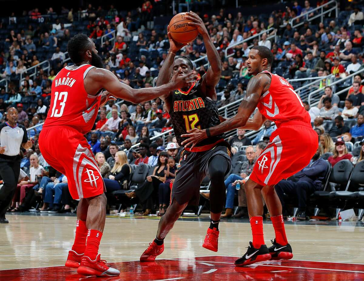 ATLANTA, GA - NOVEMBER 03: Taurean Prince #12 of the Atlanta Hawks drives between James Harden #13 and Trevor Ariza #1 of the Houston Rockets at Philips Arena on November 3, 2017 in Atlanta, Georgia. NOTE TO USER: User expressly acknowledges and agrees that, by downloading and or using this photograph, User is consenting to the terms and conditions of the Getty Images License Agreement. (Photo by Kevin C. Cox/Getty Images)
