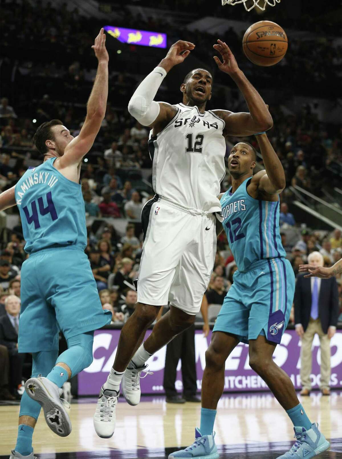 Spurs' LaMarcus Aldridge (12) gets fouled while going for a shot against Charlotte Hornets' Frank Kaminsky (44) and Dwight Howard (12) at the AT&T Center on Friday, Nov. 3, 2017. (Kin Man Hui/San Antonio Express-News)