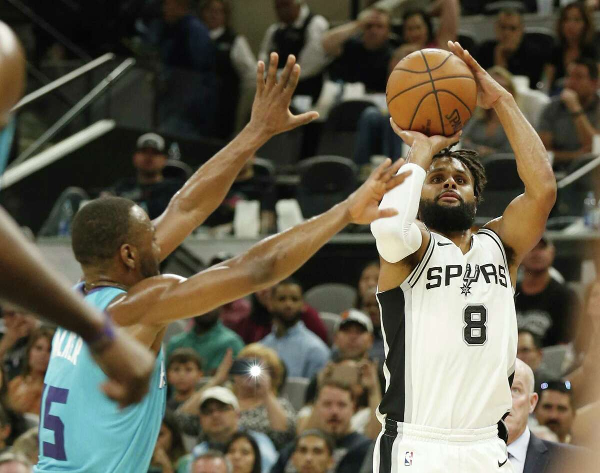 Spurs' Patty Mills (08) hits a three-pointer against Charlotte Hornets' Kemba Walker (15) in the fourth quarter at the AT&T Center on Friday, Nov. 3, 2017. Spurs defeated the Hornets, 108-101. (Kin Man Hui/San Antonio Express-News)