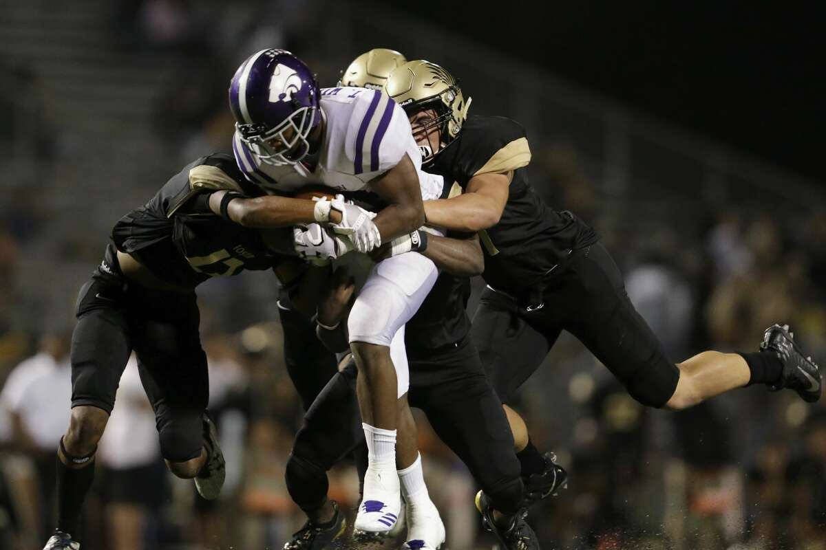 Angleton Wildcats Tamerik Williams (21) carries Foster Falcons defenders on a gain in the second half during the high school football game between Angleton Wildcats and the Foster Falcons in Rosenberg, TX on Friday, November 03, 2017. The Wildcats defeated the Falcons 34-7.