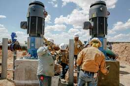 Contractors work next to two water pumps that will push water through a 20-mile pipeline at Layne Christensen's new property Tuesday, July 18, 2017 in Pecos. The Woodlands based company is building a facility to supply water for hydraulic fracturing operations in the Delaware Basin. ( Michael Ciaglo / Houston Chronicle )