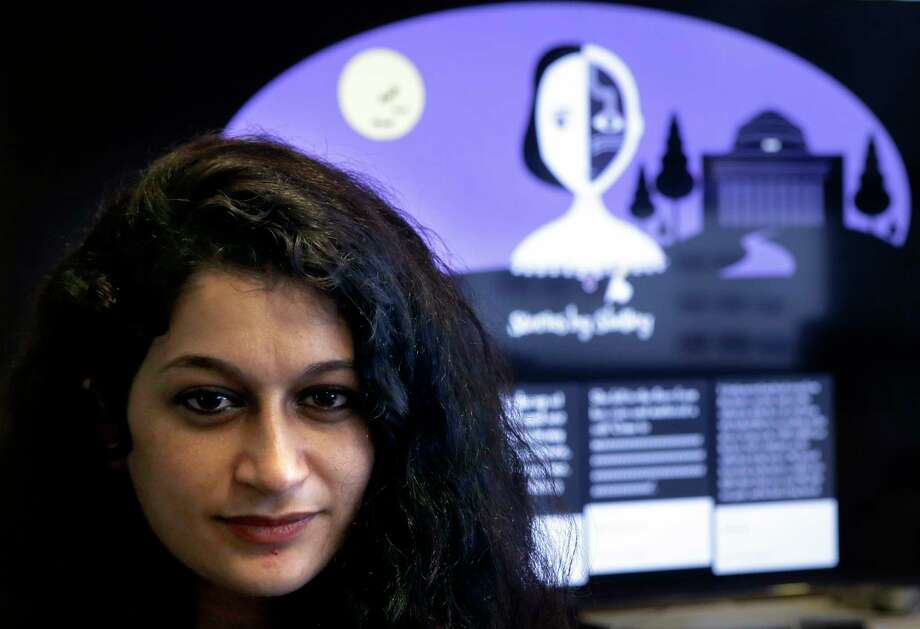 "In this Tuesday, Oct. 24, 2017 photo, co-creator of a fiction-writing 'chatbot,' Massachusetts Institute of Technology postdoctoral associate Pinar Yanardag, of Istanbul, Turkey, sits for a photograph in front of a graphic from the home page of the site called ""Shelley."" Named after ""Frankenstein"" author Mary Shelley, the chatbot has been trained on more than 140,000 horror stories written by amateur writers on a popular online forum. Now Shelley is generating its own stories on Twitter, taking turns with humans in an experiment to find out if artificial intelligence is smart enough to make someone feel scared. (AP Photo/Steven Senne) Photo: Steven Senne, STF / Copyright 2017 The Associated Press. All rights reserved."