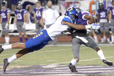 Port Neches - Groves' Khaleb Taylor is tackled by Ozen's Deon Lewis during their district mach-up at PNG Friday. Photo taken Friday, November 3, 2017 Kim Brent/The Enterprise