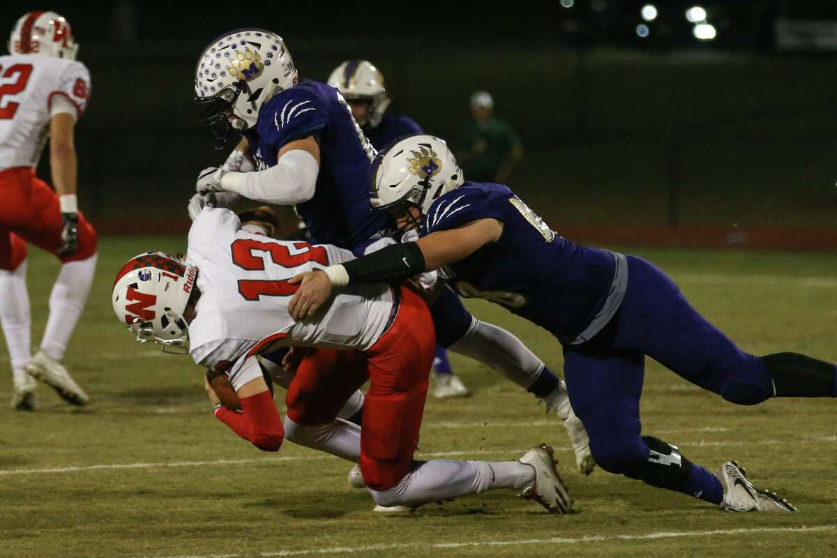 The Woodlands' Quinton Johnson (12) is tackled by Montgomery's Caleb Schneider (18) and Dayeton Sweeting (40) during the varsity football game on Friday, Nov. 3, 2017, at Bears Stadium in Montgomery. The Woodlands' Quinton Johnson (12) is tackled by Montgomery's Caleb Schneider (18) and Dayeton Sweeting (40) during the varsity football game on Friday, Nov. 3, 2017, at Bears Stadium in Montgomery. Schneider is one of the district's top players to watch this season. (Michael Minasi / Houston Chronicle)