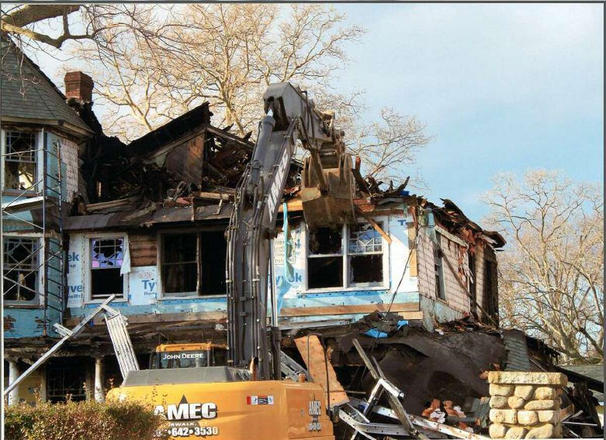 A demolition crew tears down a Shippan home one day after the fatal fire in 2011.