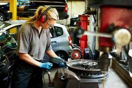 Female mechanic working on car rims in auto garage