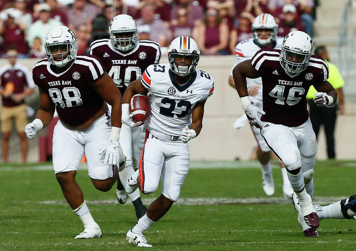 COLLEGE STATION, TX - NOVEMBER 04: Ryan Davis #23 of the Auburn Tigers rushes away from Kingsley Keke #88 of the Texas A&M Aggies and Landis Durham #46 at Kyle Field on November 4, 2017 in College Station, Texas.