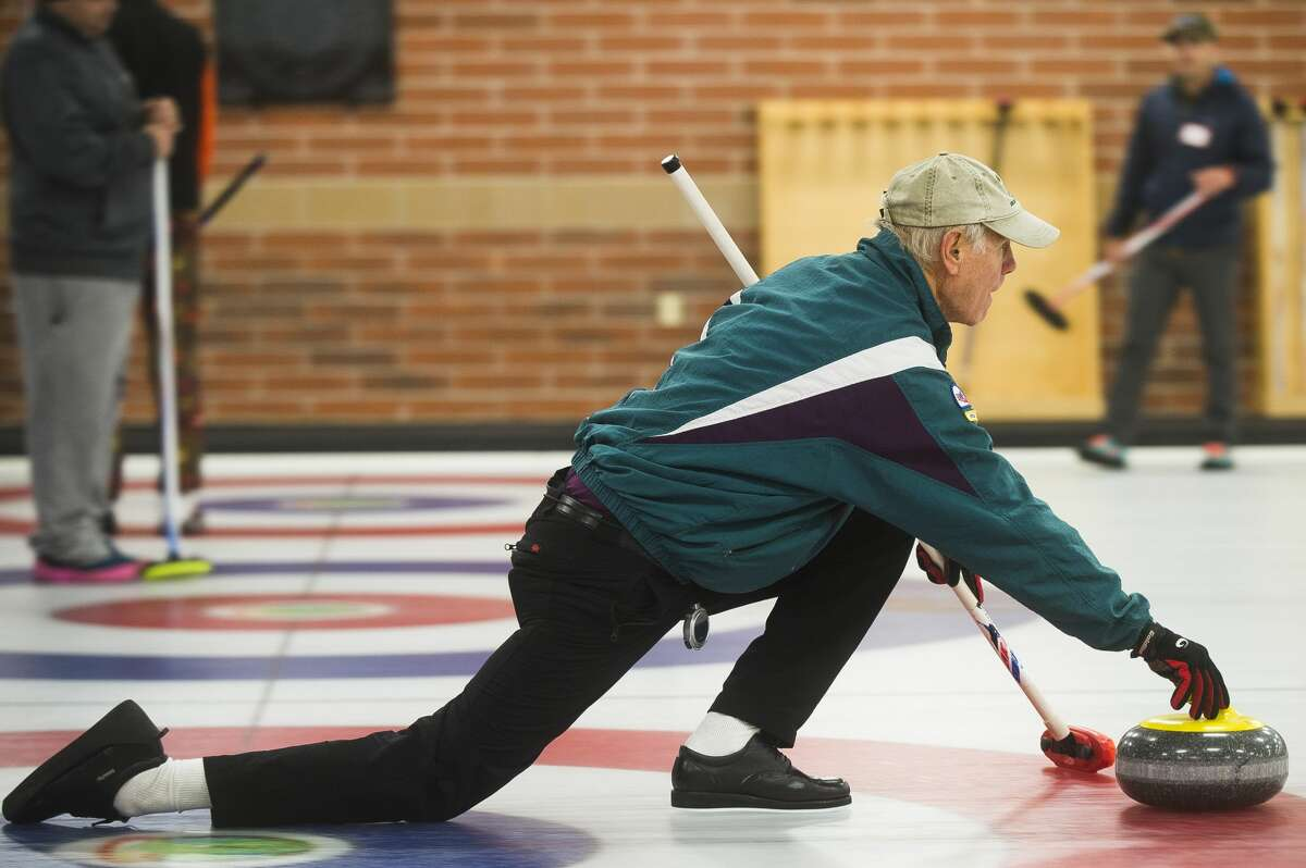 Ken Burdett of Midland throws a stone down the ice sheet during a curling open house on Saturday, Nov. 4, 2017 at the Greater Midland Curling Club. (Katy Kildee/kkildee@mdn.net)