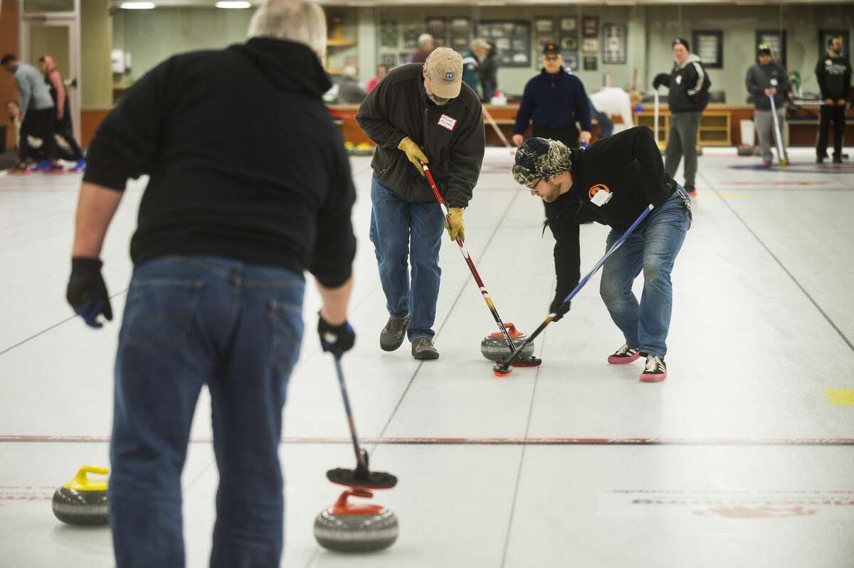 Werner Kildall of Midland, left, and Andy Wegener of Lansing, right, sweep the floor in front of their rock during a curling open house on Saturday, Nov. 4, 2017 at the Greater Midland Curling Club. (Katy Kildee/kkildee@mdn.net)