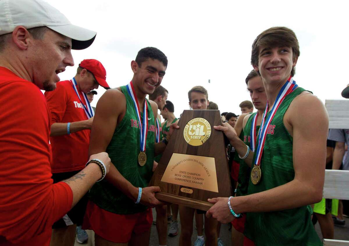 Runners with The Woodlands High School, including second overall finsher Gavin Hoffpauir (right), gather around the team's new trophy after winning the program's third straight team title and 20th overall during the UIL State Cross Country Championships at Old Settlers Park, Saturday, Nov. 4, 2017, in Round Rock.