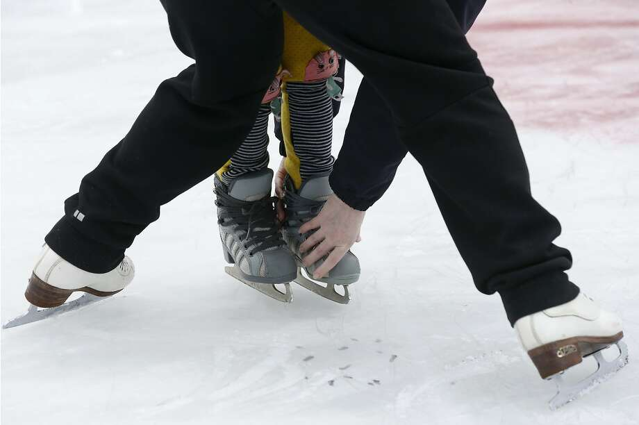 Instructor Deborah Davis helps a novice skater with foot placement during a teaching session at the Union Square rink. Photo: Paul Chinn, The Chronicle