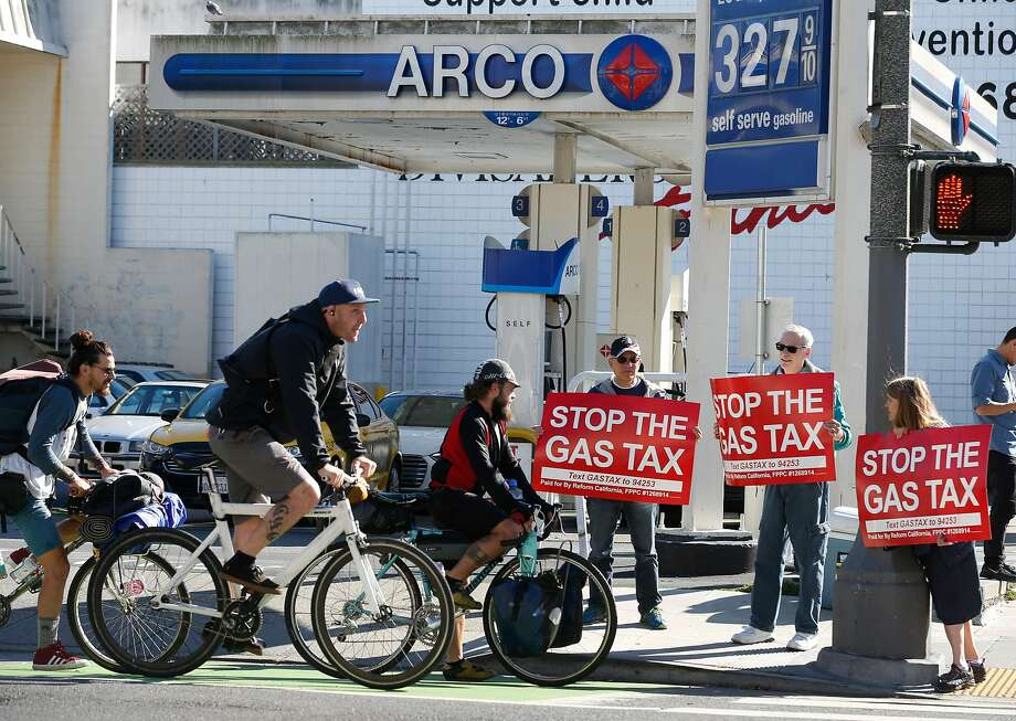 Bicyclists wait at a stop light where Barry Graynor, Howard Epstein and Lisa Remmer protest against the statewide 12-cents per gallon gas tax in front of the Arco station at Fell and Divisadero streets in San Francisco, Calif. on Saturday, Nov. 4, 2017. Photo: Paul Chinn, The Chronicle