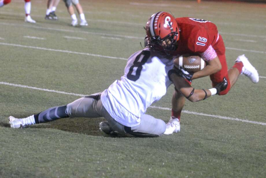 Plainview's Chris Zuniga, 16, puts his head down and gains a few extra yards as Randall's Hagen Escoto, 8, makes the tackle during a District 3-5A game at Greg Sherwood Memorial Bulldog Stadium Friday night. Photo: Skip Leon/Plainview Herald
