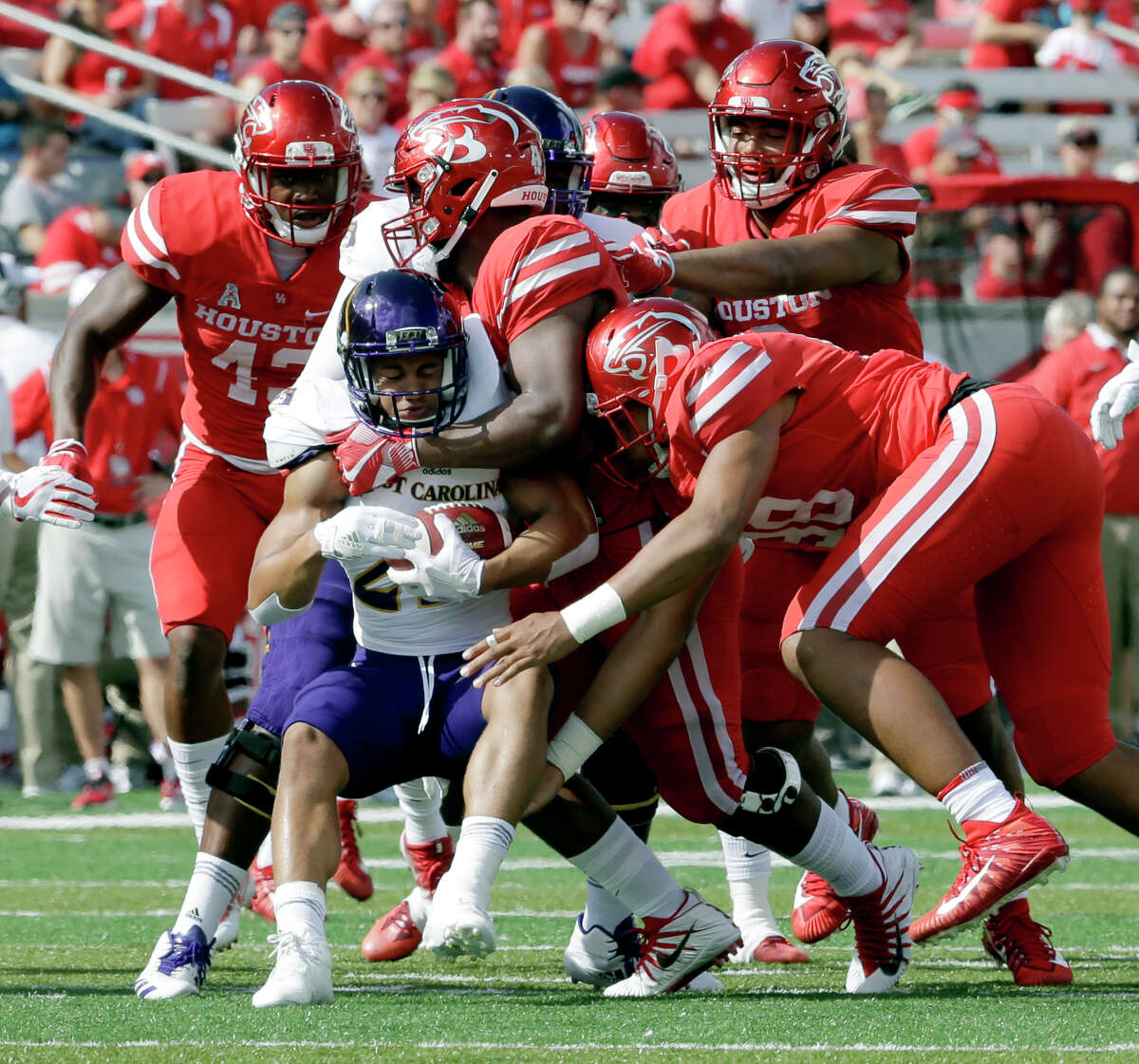 East Carolina running back Devin Anderson (25) is surrounded on a tackle by Houston's Leroy Godfrey (43), Ed Oliver (10), Emeke Egbule (8) and defensive lineman Payton Turner (98) during the first half of an NCAA college football game Saturday, Nov. 4, 2017, in Houston. (Michael Wyke/Houston Chronicle via AP)