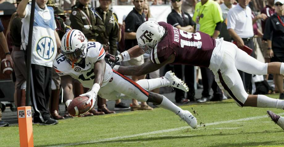 Auburn wide receiver Eli Stove (12) dives for the end zone for a touchdown as Texas A&M linebacker Anthony Hines III (19) defends during the second half of an NCAA college football game on Saturday, Nov. 4, 2017, in College Station, Texas. (AP Photo/Sam Craft) Photo: Sam Craft/Associated Press