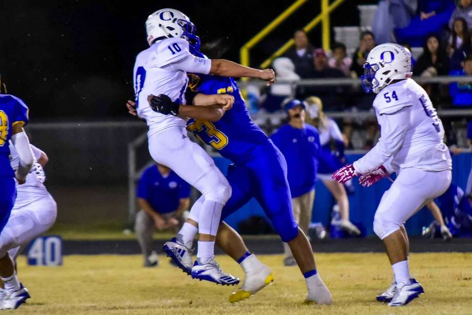 Hale Center defensive lineman Quentin Bendele hits Olton quarterback Jack Allcorn, 10, as Olton offensive lineman Alberto Sinaloa, 54, looks on during a District 2-2A, Division I game at Hale Center Friday night. Photo: Photo Courtesy Of Albert Gomez Photography