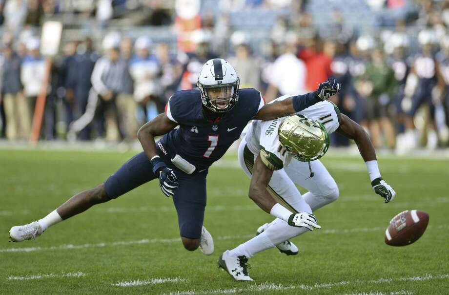 UConn's Hergy Mayala, left, and South Florida's Marquez Valdes-Scantling try to track down a pass in the first half Saturday in East Hartford. Photo: Stephen Dunn / Associated Press / FR171426 AP