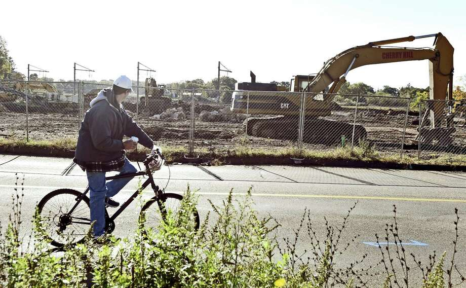 Branford,  Connecticut - Friday, October 27, 2017:  A bicyclist passes by 301 Meadow Street in Branford, as the former Atlantic Wire is demolished to make way for a new mixed development called Atlantic Wharf. Photo: Peter Hvizdak / Hearst Connecticut Media / New Haven Register