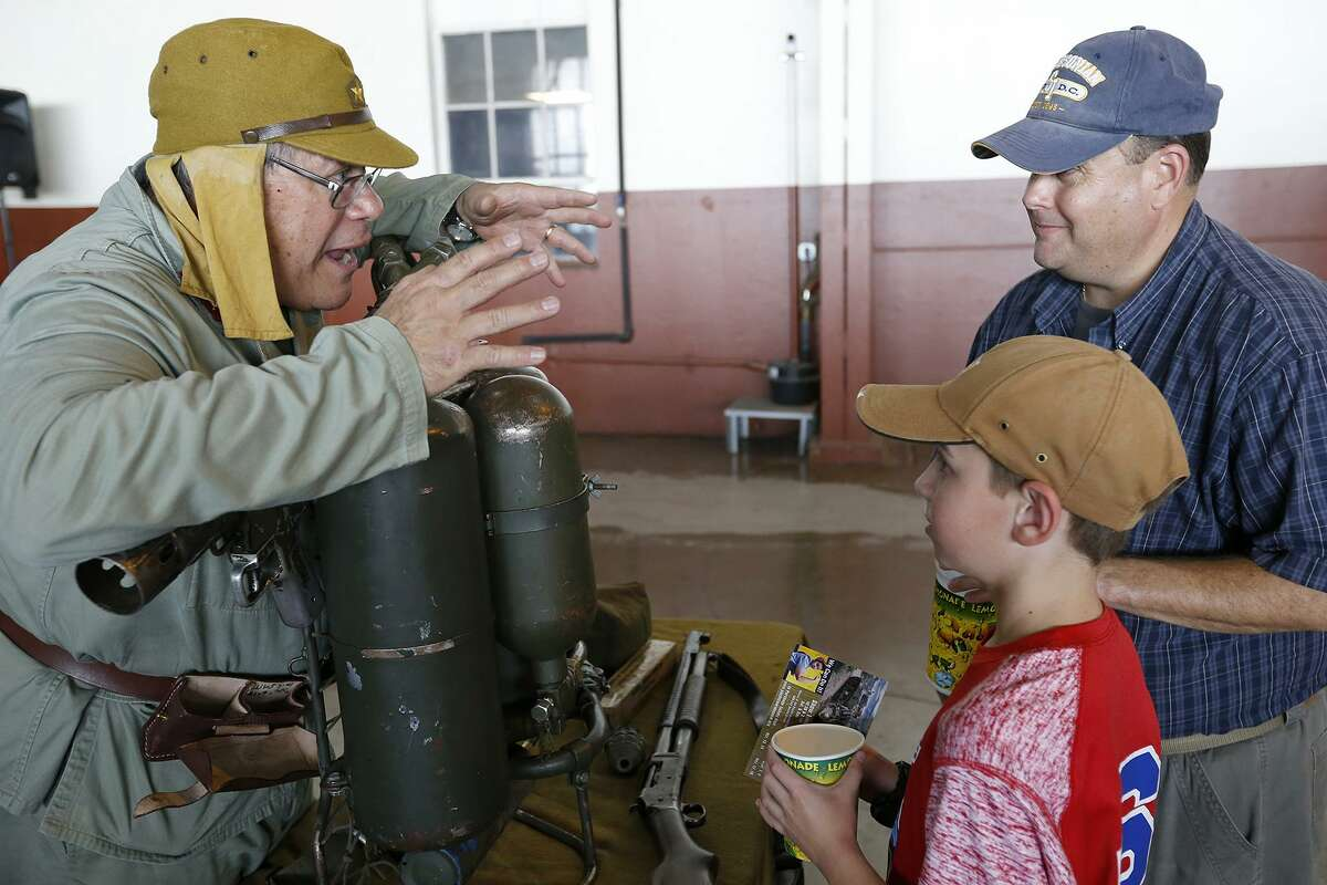 National Museum of the Pacific War volunteer Reginald L. Smith (left) shows Michael Johnson and his son Cody,10, a World War II flamethrower during the the Joint Base San Antonio 2017 Air Show and Open House held Saturday Nov 4, 2017 at JBSA-Lackland Kelly Field Annex at Port San Antonio.