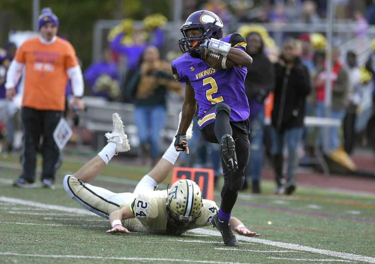 Westhill Noldylens Metayer (2) breaks up the sidelines past Trumbull's Alexander Moran (24) to run in for a Viking touchdown in a FCIAC boys football game at Westhill High School in Stamford, Connecticut on Saturday, Nov. 4, 2017. Westhill defeated Trumbull 29-21.