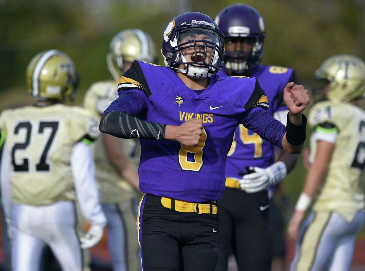 Westhill quarterback AJ Laccona (8) celebrates following a touchdown against Trumbull by teammate Angelo Nicholas (10) in a FCIAC boys football game at Westhill High School in Stamford, Connecticut on Saturday, Nov. 4, 2017.