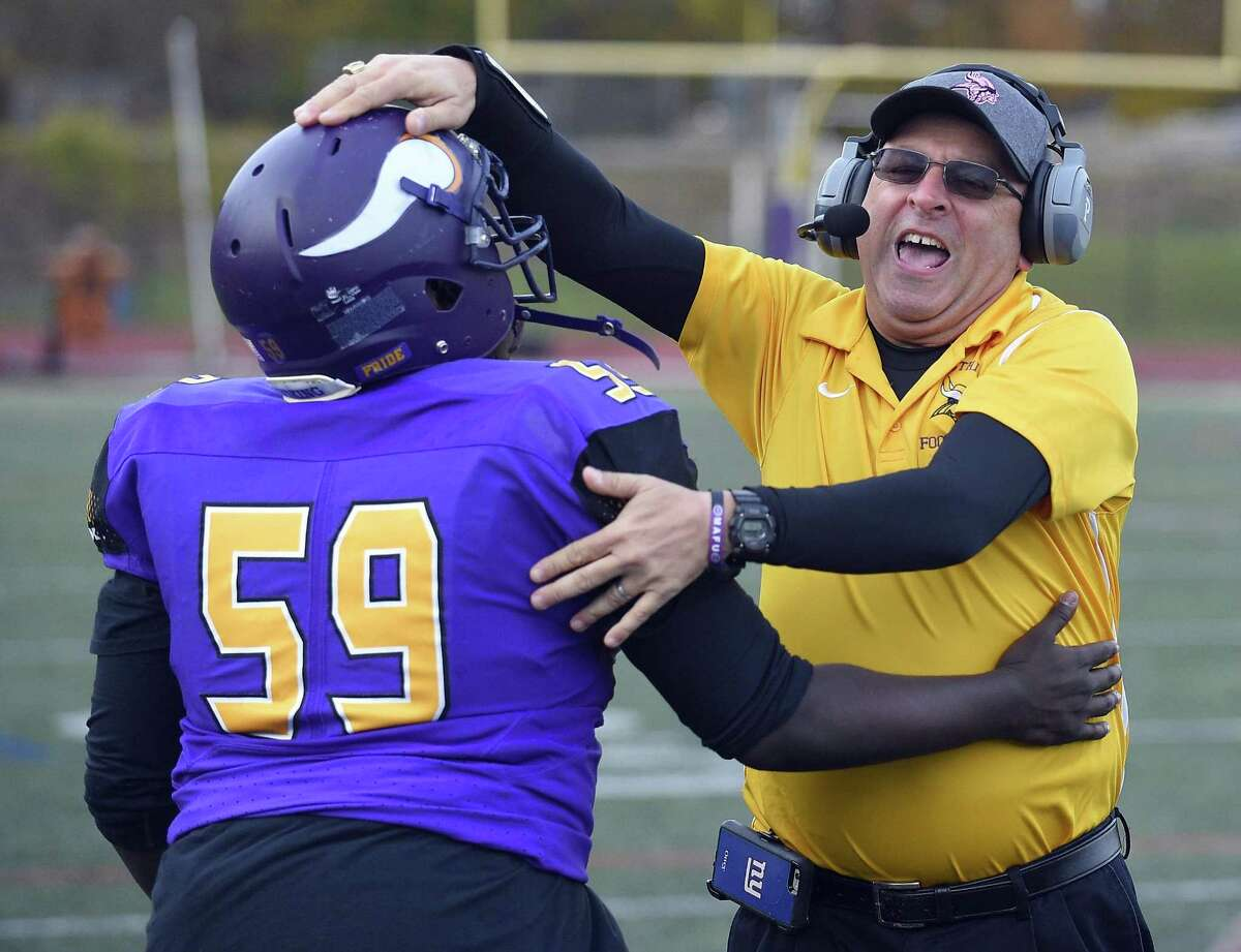 Westhill coach Frank Marcucio (in yellow) celebrates his teams 29-21 win over Trumbull with Peter Leandre (59) in a FCIAC boys football game at Westhill High School in Stamford, Connecticut on Saturday, Nov. 4, 2017.