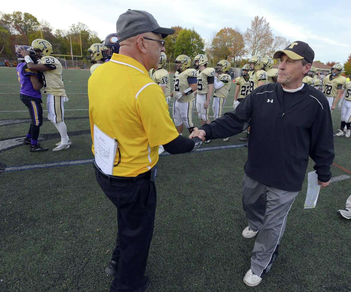 Westhill coach Frank Marcucio (in yellow) shakes hands with Trumbull coach Bob Maffei following the Vikings 29-21 win in a FCIAC boys football game at Westhill High School in Stamford, Connecticut on Saturday, Nov. 4, 2017.