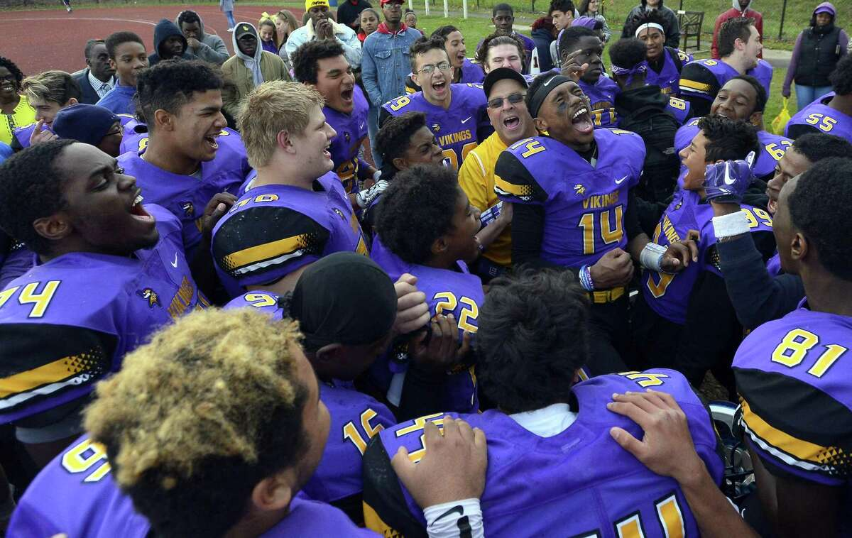 Westhill coach Frank Marcucio (in yellow) celebrateswith his players after the Vikings 29-21 win over Trumbull in a FCIAC boys football game at Westhill High School in Stamford, Connecticut on Saturday, Nov. 4, 2017.