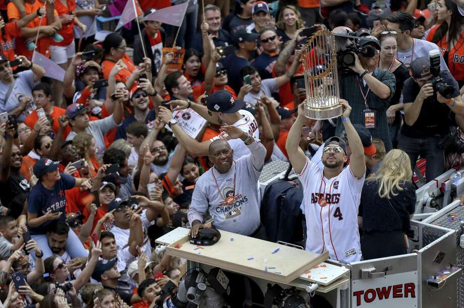 Houston Astros right fielder George Springer holds up the World Series trophy during s parade for the champion Astros Friday in Houston. Photo: Jon Shapley / Associated Press / ' 2017 Houston Chronicle