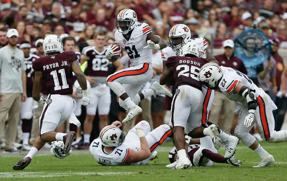 COLLEGE STATION, TX - NOVEMBER 04: Kerryon Johnson #21 of the Auburn Tigers hurdles over Braden Smith #71 as Larry Pryor #11 of the Texas A&M Aggiess and Tyrel Dodson #25 attempts to make a tackle at Kyle Field on November 4, 2017 in College Station, Texas. (Photo by Bob Levey/Getty Images)