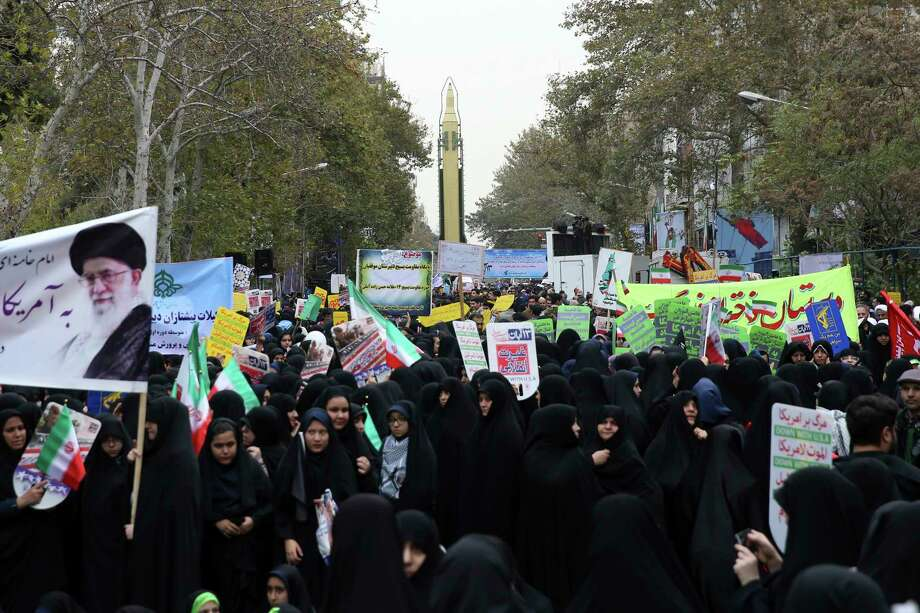 Iranian demonstrators attend an annual gathering in front of the former U.S. Embassy marking the anniversary of its 1979 takeover, while a surface-to-surface missile is displayed by the Revolutionary Guard, at rear, in Tehran, Iran, Saturday, Nov. 4, 2017. Iran on Saturday displayed a surface-to-surface missile as part of events marking the anniversary of the 1979 U.S. Embassy takeover and hostage crisis amid uncertainty about its nuclear deal with world powers. (AP Photo/Vahid Salemi) Photo: Vahid Salemi, STR / Copyright 2017 The Associated Press. All rights reserved.