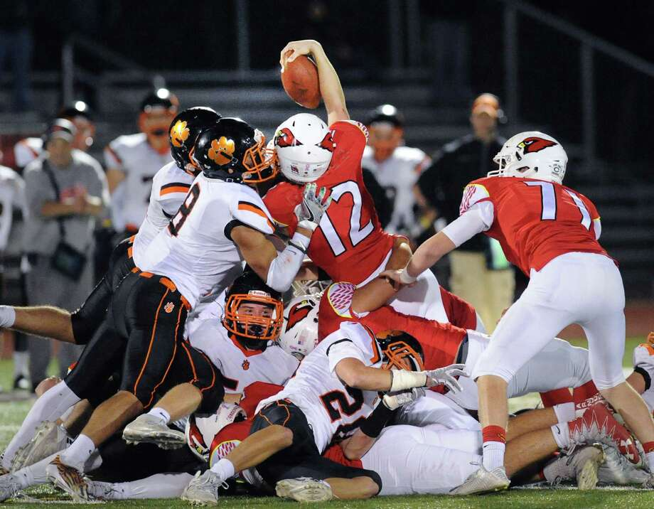 Greenwich quarterback Gavin Muir, top with ball, can not be denied by the whole Ridgefield defense, including Jackson Mitchell (#8), left,  as Muir reaches for and gets a first-down on a fourth and inches in the final minutes of play sealing a 26-21 victory over Ridgefield during the high football game between Ridgefield High School and Greenwich High School at Cardinal Stadium in Greenwich, Conn., Saturday, Nov. 4, 2017. Photo: Bob Luckey Jr., Hearst Connecticut Media / Greenwich Time