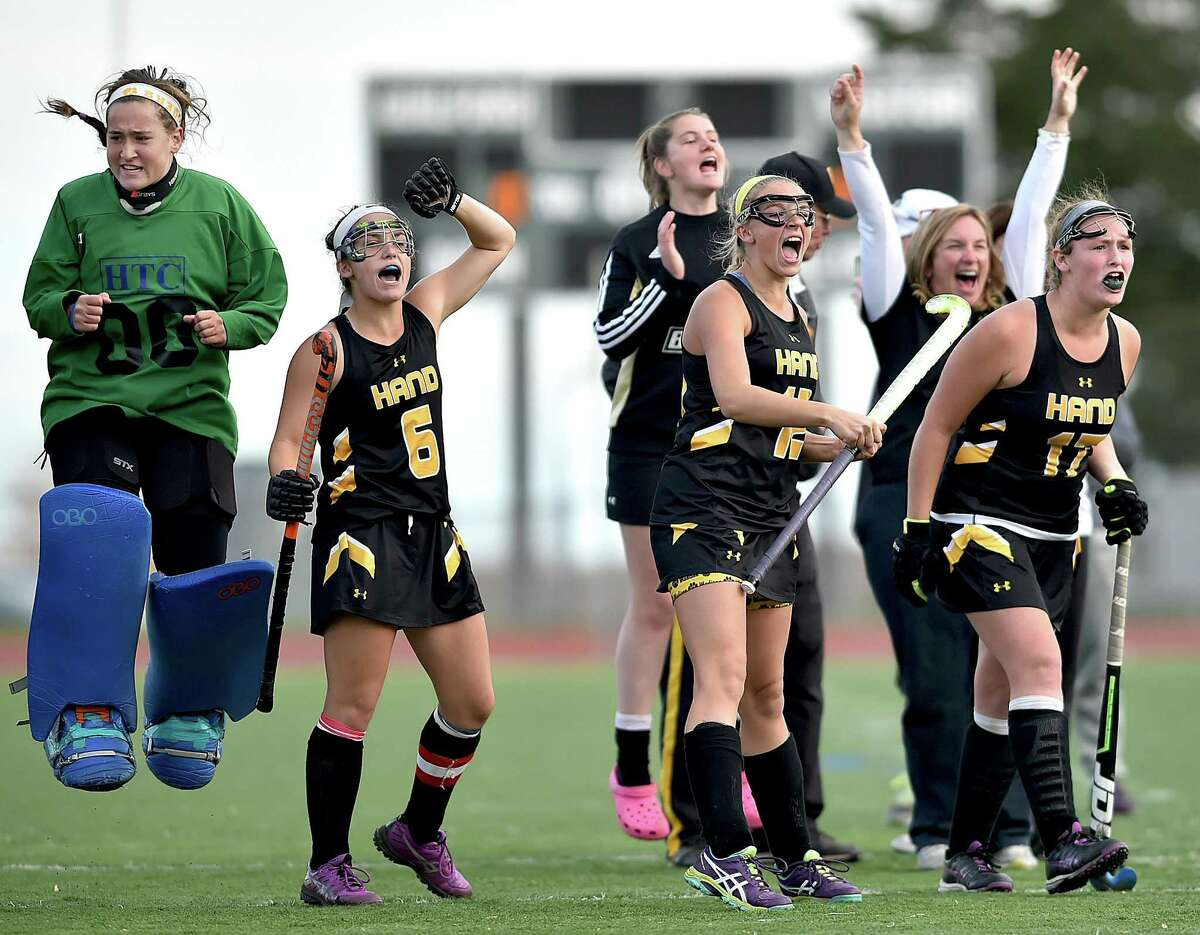 Hand players celebrate after one of their teammates scored during penalty strokes in their victory over Branford in the SCC field hockey championship game Saturday in Guilford.
