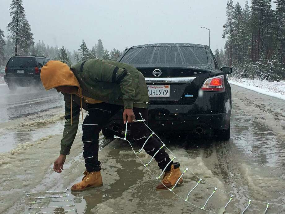 Ivory Williams of Sacramento removes chains from her friend's car during a snowstorm near Kingvale, Calif., on Saturday. Photo: Juliet A. Williams, STF / Copyright 2017 The Associated Press. All rights reserved.