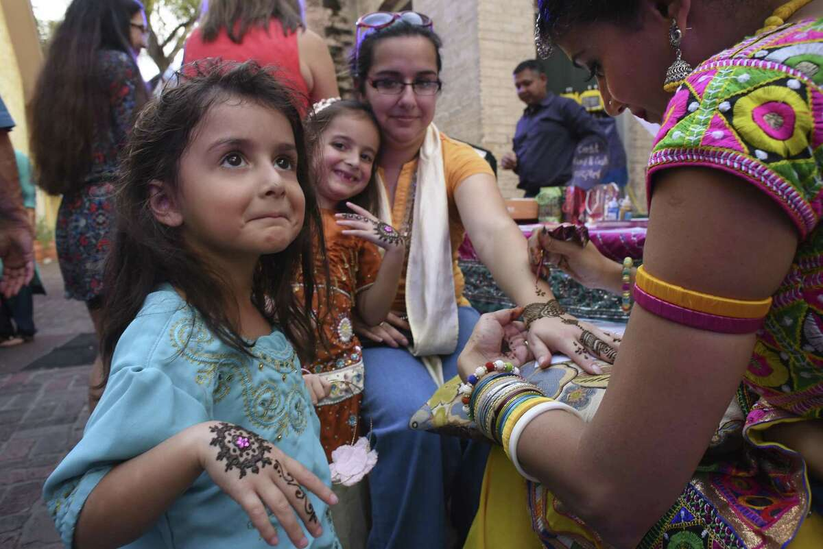 Adelaide Gamboa, front, and her sister, Penelope, display their henna tattoos as their mother, Jaclyn, receives a tattoo of her own from Paullomi Patel, right, during the Diwali San Antonio Festival of Lights at La Villita on Saturday, Nov. 4, 2017. Diwali is India's most important holiday, and celebrates victory of good over evil.