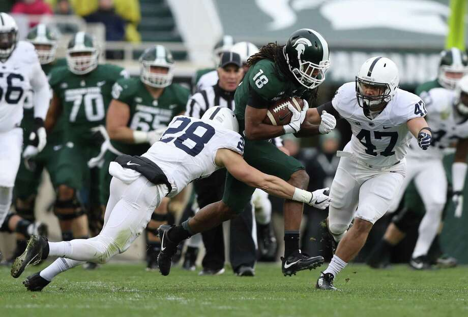 Michigan State's Felton Davis III, center, makes a run for it with after a reception as Penn State's Troy Apke, left, and Brandon Smith close in during first-quarter action Saturday. Photo: Kirthmon F. Dozier, MBR / Detroit Free Press